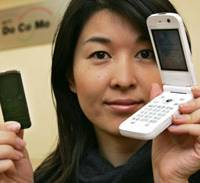 Tomoko Tsuda of NTT DoCoMo Inc. displays the new mobile phone P903i with its security key card feature Thursday in Tokyo. To protect the phone if it's lost or stolen, the P903i locks itself when it cannot read the signal from the key. | AP PHOTO