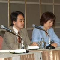 Yoshiaki Hotaka (left), an editorial page writer for the Yomiuri Shimbun, and Hiroko Kiba, who served as coordinator for the Oct. 18 session, listen to the discussions.