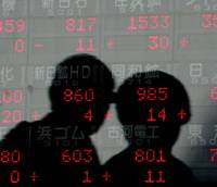 Passersby are silhouetted on the glass of an electronic stock quotation board in Tokyo. | AP PHOTO