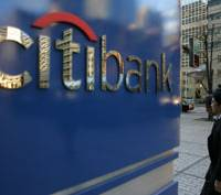 A man passes a Citibank signboard Tuesday in Tokyo. | AP PHOTO