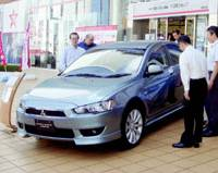Pedestrians check out Mitsubishi Motors Corp.'s sporty new Gallant Fortis sedan in front of the carmaker's headquarters in Minato Ward, Tokyo, last week. | KYODO PHOTO