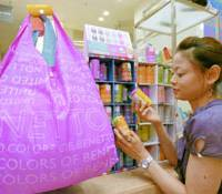 A woman checks out 'eco-bags' from Italy's Benetton at a shop in Tokyo's Omotesando district last month. | KYODO PHOTO