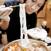 A woman eats 'udon' noodles used as an ingredient for a popular Chinese dish called 'huo guo' at an Osaka restaurant earlier this month. | KYODO PHOTO