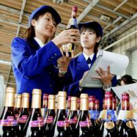Customs officials check the first shipment of Beaujolais Nouveau at Chubu Centrair International Airport Friday. The young French wine will be uncorked nationwide at midnight Wednesday. | KYODO PHOTO