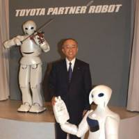 Toyota Motor Corp. President Katsuaki Watanabe shows off the company's new Robina robot, which can hold objects with its three fingers and has a 20,000-word vocabulary, in Koto Ward, Tokyo, on Thursday. | SATOKO KAWASAKI PHOTO