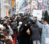 Thousands of shoppers line up at the Matsuya department store in Tokyo's Ginza district Wednesday, waiting for the store to open for the first time this year.   SATOKO KAWASAKI PHOTO