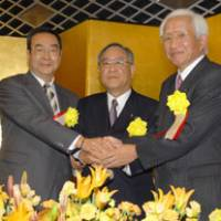 The leaders of the three major business organizations, (from left) Masamitsu Sakurai of the Japan Association of Corporate Executives (Keizai Doyukai), Fujio Mitarai of the Japan Business Federation (Nippon Keidanren) and Tadashi Okamura of the Japan Chamber of Commerce and Industry, clasp hands at a joint news conference in Tokyo on Monday. | YOSHIAKI MIURA PHOTO
