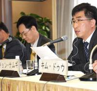 Chung Nam Ki (right) of The Hankyoreh newspaper speaks about South Korea's economic challenges while his co-panelists Jang Gyeong Duk (second from left) and Rhee Hak Young listen. | SATOKO KAWASAKI PHOTO