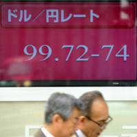 Pedestrians walk past an exchange rate sign in Tokyo Wednesday morning. | AP PHOTO
