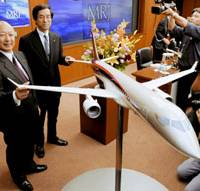 Flying high: Mitsubishi Heavy Industries Ltd. Chairman Kazuo Tsukuda (left) smiles during a news conference in Tokyo in March to announce that the Mitsubishi Regional Jet would go into commercial production.   KYODO PHOTO