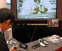 Action figure: A man looks at Osamu Tezuka's motion magazine on a digital music player at Alpha Systems Inc.'s booth at the Digital Publishing Fair at Tokyo Big Sight on Thursday. | KAZUAKI NAGATA PHOTO