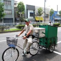 Making the rounds: Yusuke Sakurai, an employee of a Yamato Transport Co. service center in Koto Ward, Tokyo, uses an electric bicycle to deliver parcels on Aug. 4.   HIROKO NAKATA PHOTO
