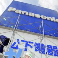 Out with the old: Workers take down the Matsushita sign from Matsushita Electric Industrial Co.'s headquarters in Kadoma, Osaka Prefecture, last week as the company prepared to change its corporate name to Panasonic Corp. | KYODO PHOTO