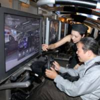 Hammer down: A reporter tries out Sony Computer Entertainment Inc.'s 'Gran Turismo 5 Prologue Spec III' at Tokyo Game Show 2008 in Chiba Prefecture on Thursday. | YOSHIAKI MIURA PHOTO