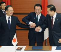 Squeeze test: Prime Minister Taro Aso clenches the hands of Chinese Premier Wen Jiabao (left) and of South Korean President Lee Myung Bak at Kyushu National Museum after their Saturday summit. | KYODO PHOTO