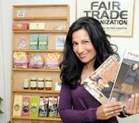 It's a deal: Safia Minney, founder of Fair Trade Co., holds up catalogs for the company's People Tree brand products at her office in Setagaya Ward, Tokyo. | SATOKO KAWSAKI PHOTO
