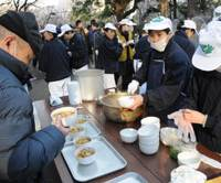 Helping hand: A homeless man receives free food from volunteer workers at the tent village set up at Hibiya Park in Chiyoda Ward, Tokyo, on Jan. 5. | SATOKO KAWSAKI PHOTO