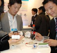 Sweet power: A Sony Corp. employee demonstrates a 'bio battery' that generates electricity from sugar by squeezing a drop of Coca-Cola on it at the 5th International Hydrogen & Fuel Cell Expo. | YOSHIAKI MIURA PHOTO