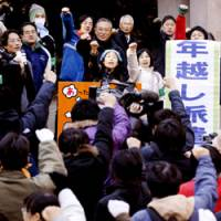 In solidarity: Homeless people punch the air during a ceremony to mark the opening of a shelter village in Hibiya Park for the homeless on Dec. 31 in Chiyoda Ward, Tokyo. | KYODO PHOTO