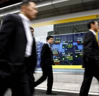 Don't look now: Pedestrians pass by an electronic board showing Monday's stock prices on the Tokyo Stock Exchange, where the Nikkei index ended at a 26-year-low.   AP PHOTO