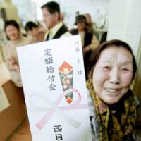 Spending money: A woman at the municipal office in Nishimeya, Aomori Prefecture, holds up an envelope containing a government cash handout Thursday. | KYODO PHOTO