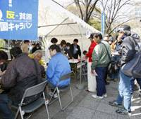 Helping hand: Lawyers and union members give jobless people assistance in front of Osaka City Hall on Saturday.   KYODO PHOTO