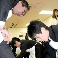 Time to shine: Takashi Suzuki, a new hire at Columbus Co., a Tokyo-based shoe products maker, shines a senior worker's shoe at the firm's welcoming ceremony Wednesday. Every April 1, hundreds of thousands of young recruits start their careers nationwide.   SATOKO KAWSAKI PHOTO