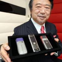Off the hook: Yoichiro Ban, president of Vertu, shows off some of his company's luxury mobile phones at the company's store in Tokyo's Ginza district on April 2. | YOSHIAKI MIURA PHOTO