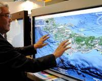 World at his fingers: An official of EIT Co. shows how to rotate a map of Japan using the company's touch screen, which was displayed Wednesday at Tokyo Big Sight in Koto Ward. (See a video of the event at the bottom of the story.) | SATOKO KAWSAKI PHOTO