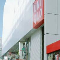 Turf war: People walk by a new Uniqlo outlet that opened Friday on the west side of JR Shinjuku Station in Tokyo. | KYODO PHOTO
