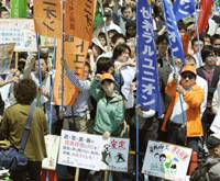 Up in arms: Regular and temporary workers hold banners calling for wage hikes and job security during the 80th annual May Day rally organized by the Japanese Trade Union Confederation (Rengo) on Wednesday in Tokyo's Yoyogi Park. | KYODO PHOTO