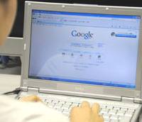 Searching for an answer: An office worker calls up Google's Web site on her laptop computer Tuesday. The Internet search giant is facing challenges from the success of social networking sites such as Facebook. | SATOKO KAWSAKI PHOTO