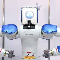 Bot time to flip it: Okonomiyaki Robot, developed by Osaka-based Toyo Riki Co., flips 'okonomiyaki' — Osaka's signature pancake — Tuesday at the International Food Machinery and Technology Exhibition at Tokyo Big Sight in Koto Ward. | SATOKO KAWSAKI PHOTO