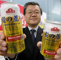 Priced to move: Kunihiko Hisaki, Aeon's chief merchandising officer, holds a 350-ml can of the company's new Topvalu Mugi No Kaori beerlike drink, priced at ¥100, and a 500-ml can that will retail for ¥145, in Tokyo on Monday. | KYODO PHOTO