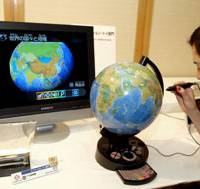 Globe-trotter: A woman demonstrates how to use Epoch Co.'s TV Globe, the winner of the Japan Toy Association's award for innovative products, in Tokyo Tuesday. With the touch of a pen, information about a specific location is displayed on a television screen. | YOSHIAKI MIURA PHOTO