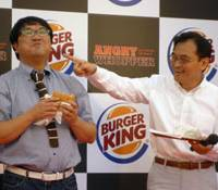 Spicing things up: Burger King Japan President Hitoshi Arimoto (right) watches as comedian Cunning Takeyama eats an Angry Whopper, the fast-food chain's latest burger, during a promotional event in Tokyo on Wednesday. | AP PHOTO
