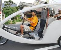 The scenic route: Fumiyuki Imaoka, 42, a retired chef who landed a job as a Velotaxi driver after being rejected by several companies, takes tourists on a recent ride around Izumo Grand Shrine in Shimane Prefecture. | KYODO PHOTO