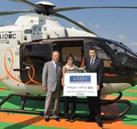 High-end service: (From left) Mori Building City Air Services Co. President Kazuhisa Shin, Dora Chong, the general manager of cosmetic company Coty Prestige Southeast Asia, and Grand Hyatt Tokyo General Manager Christophe Lorvo pose in front of a helicopter on the roof of the Ark Mori Building in Minato Ward, Tokyo, on Wednesday. | YOSHIAKI MIURA PHOTO