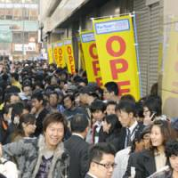 Ready to deal: Thousands of people wait for Yamada Denki Co.'s new Tokyo flagship store to open Friday in the Ikebukuro district.   KYODO PHOTO