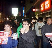 Sale sweeteners: Customers awaiting the 6 a.m. start of a sale at Uniqlo's flagship Ginza store in Tokyo on Saturday tuck into sweet bean-paste buns and milk provided by the company. | KYODO PHOTO