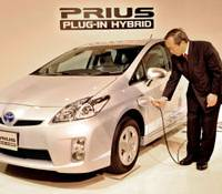 Home appliance?: Takeshi Uchiyamada, executive vice president at Toyota Motor Corp., shows the plug-in version of the Prius hybrid during its unveiling Monday. | YOSHIAKI MIURA PHOTO