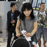 A step ahead: Yuko Hirohara, wife of a Japanese company worker in Bangkok, prepares Wednesday to fly out of Suvarnabhumi International Airport with her son to temporarily evacuate the flood-hit Thai capital. | KYODO