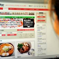 Don't cook tonight: A woman checks out the fineDine website, where various dishes from well-known restaurants in Tokyo are listed for delivery and and can be ordered online. | YOSHIAKI MIURA PHOTO