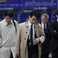 Downcast: Pedestrians cross an intersection in central Tokyo last week. The Bank of Japan's 'tankan' survey released Thursday indicates confidence at major manufacturers fell over the last quarter. | AP PHOTO