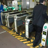 Without a glitch: A man enters an IC-card ticket gate at a JR East station in Chiyoda Ward, Tokyo, on Aug.14. | KYODO