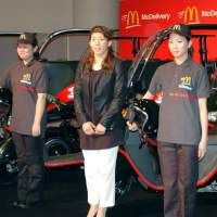 Faster food: Olympic gold medal wrestler Saori Yoshida (center) promotes the McDonald's home delivery service during an event in Tokyo in November. | KYODO