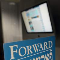The new orthodoxy: A monitor displaying the Forward's new website is seen behind a sign on the door of the newspaper's office in lower Manhattan on Friday. | AFP-JIJI