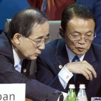 Finance Minister Taro Aso (right) listens to Bank of Japan Gov. Masaaki Shirakawa during a meeting of finance chiefs of the Group of 20 countries in Moscow Saturday. | AP