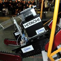 Stair master:  The  Tsubaki robot, developed by a startup firm of the Chiba Institute of  Technology and carrying a camera developed by Hitachi Ltd., climbs a set of stairs during a demonstration in Chiba Prefecture on Wednesday.   YOSHIAKI MIURA