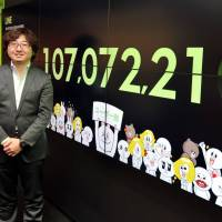 Line drive hit: NHN Japan Corp. CEO Akira Morikawa stands in his office in Tokyo on Feb. 5, with the number of Line users proudly on display. | YOSHIAKI MIURA